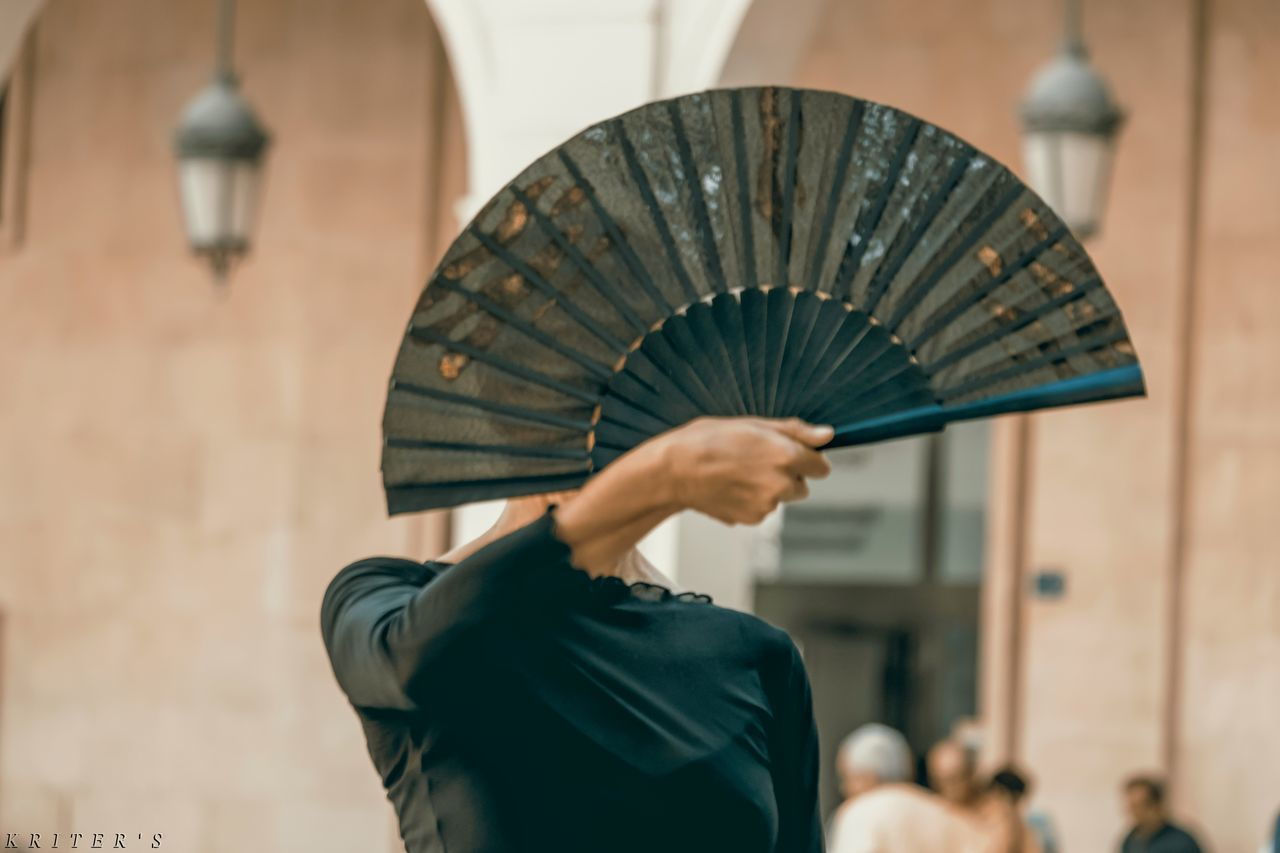 hand fan, real people, umbrella, adult, people, rear view, focus on foreground, women, holding, protection, lifestyles, waist up, security, men, architecture, standing, day