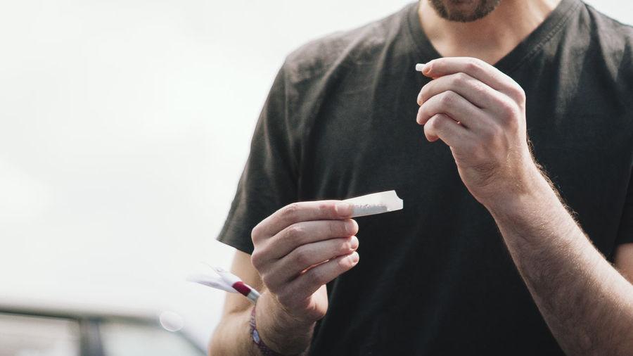 Midsection Of Man Making Marijuana Joint