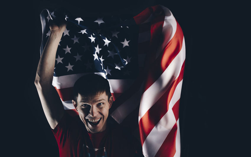 Patriotism One Person Studio Shot Emotion Flag Portrait Looking At Camera Front View Black Background Happiness Real People Sport Indoors  Young Adult Smiling Red Human Arm Positive Emotion Excitement Arms Raised My Best Photo 17.62° The Portraitist - 2019 EyeEm Awards