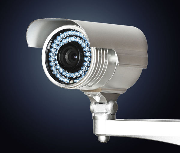 Close-up of security camera against gray background