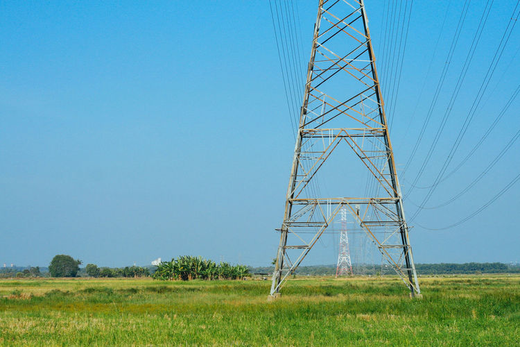 Substations over the blue sky Clear Sky Day Electricity  Electricity Pylon Field Grass Landscape Nature No People Outdoors Tree