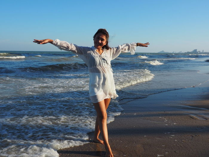 Full length of happy woman standing on beach