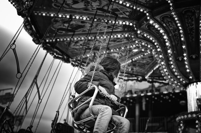 Girl Sitting In Carousel At Amusement Park