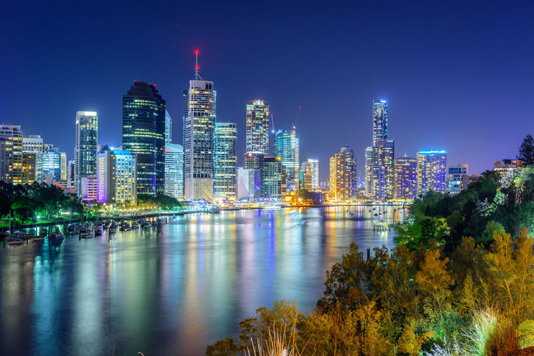 Illuminated Buildings By River In City Against Sky At Night
