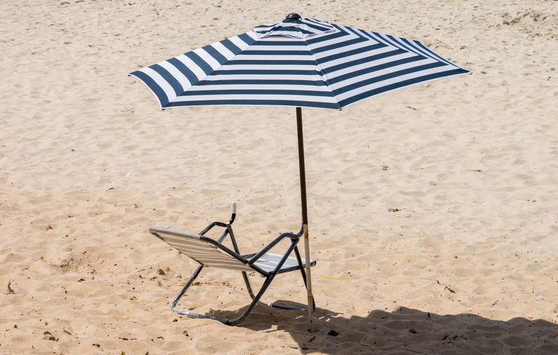 High angle view of deck chair and parasol on sandy beach during sunny day