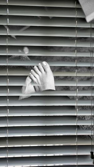 Close-up of hands against closed window