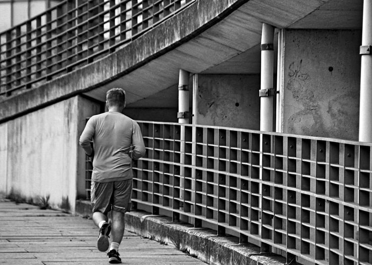 Rear view of man jogging on footpath in city