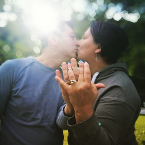 Close-Up Of Mature Couple Showing Wedding Rings While Kissing At Park