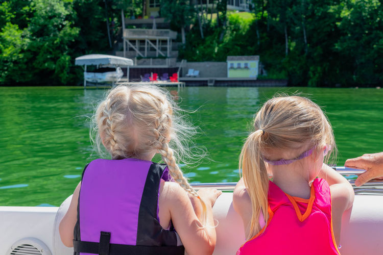 Back view of two little girls on a boat on summer vacation Back View Boating Kids Lake Life Lifestyle Summer Vacation Summertime Blond Hair Boat Childhood Day Girls Headshot Lake Leisure Activity Life Vest Outdoors People From Behind Real People Recreational Pursuit Safety Summer Summer Lifestyle Water Water Sports
