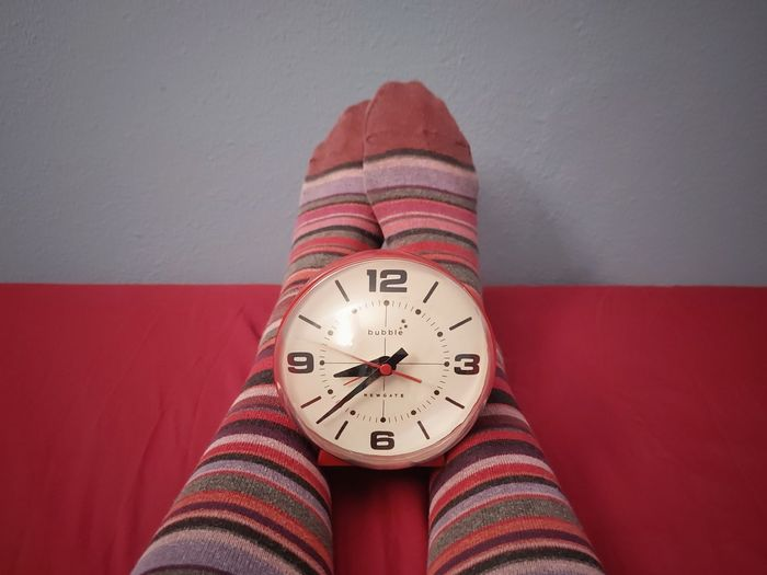 Low angle view of clock on red wall