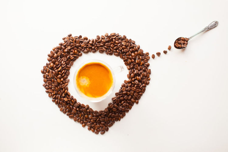 Coffee cup with fresh brewed coffee and brown roasted coffee beans in a heart shape on white background top flat lay view Food And Drink Food Indoors  White Background Freshness Still Life Healthy Eating Wellbeing Refreshment Studio Shot Directly Above Brown Drink No People Copy Space High Angle View Close-up Coffee Coffee - Drink Table Breakfast Egg Yolk