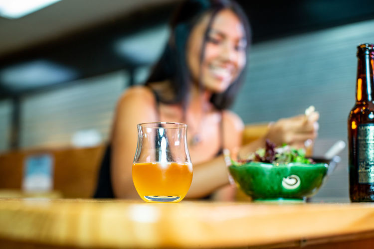 Low angle view of woman with food and drink on table in restaurant