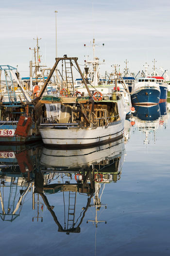 Boats moored at harbor with reflection in sea against sky