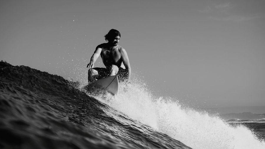 Man surfing on sea against sky