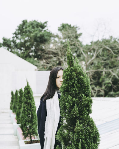 Young woman standing by tree