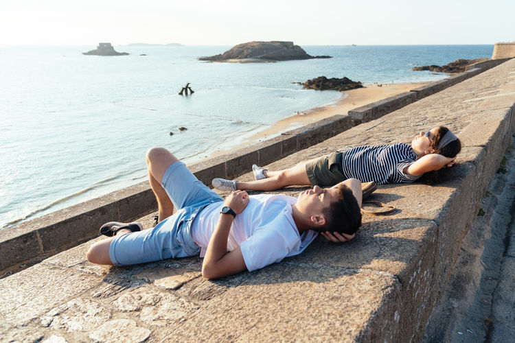 Coyuple lying on wall resting facing the sun against ocean Real People Lifestyles Lifestyle People Young Millenials Couple Water Lying Down Sea Full Length Beach Casual Clothing Nature Leisure Activity Day Relaxation Lying On Back Young Adult Two People Sunlight Outdoors Togetherness Love