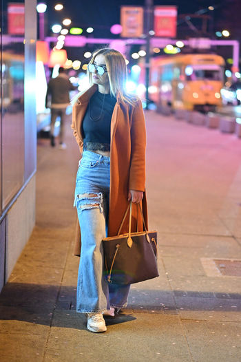 Woman with umbrella walking on street at night