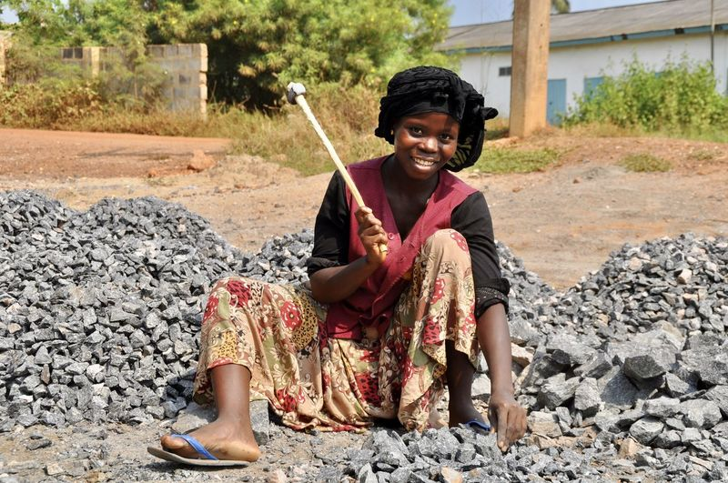 Portrait of smiling female woman breaking gravels