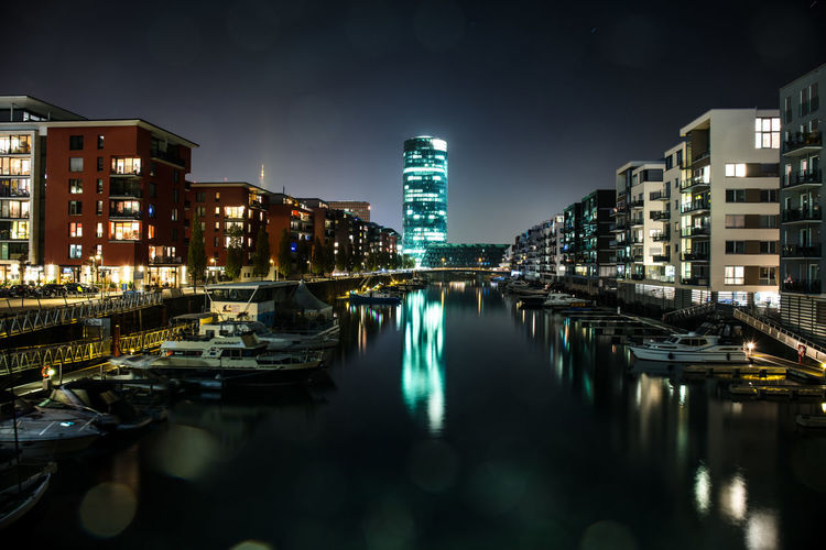 Boats moored in canal against illuminated buildings in city at night