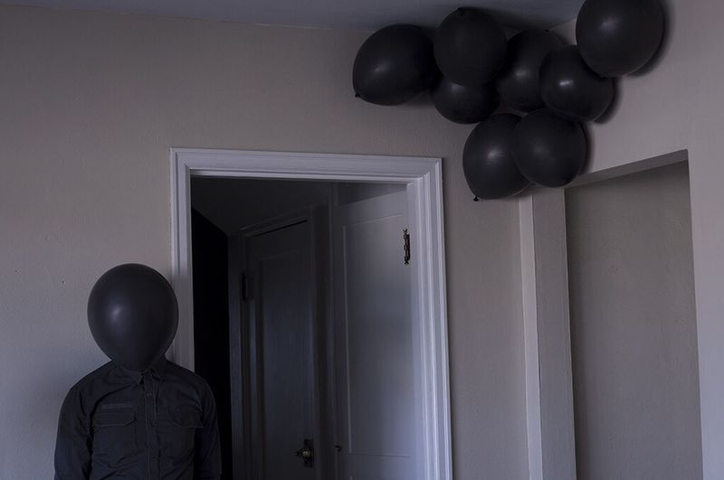 Balloon Obscuring Face Of Man In House
