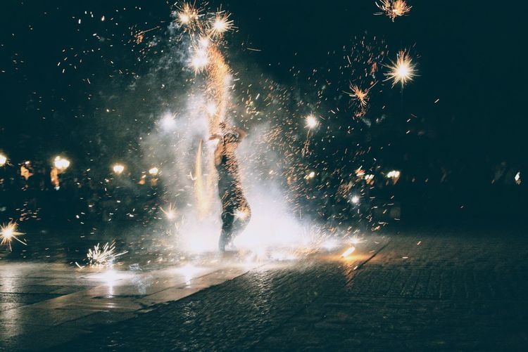 Man standing amidst fireworks at night
