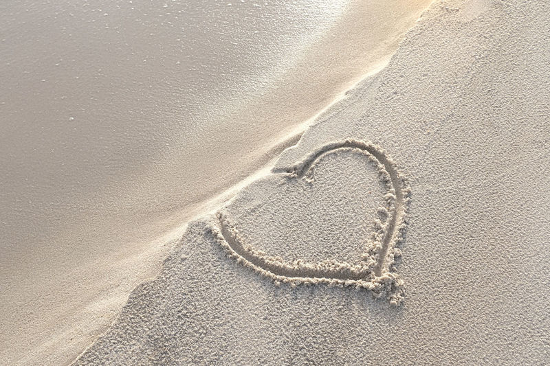 Heart shape hand written in the sand on the beach. love in danger and in difficulty. sad message.