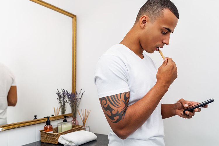 One Person Indoors  Real People Holding Standing Leisure Activity Technology Looking Smarthphone Bathroom Brushing Teeth Lifestyles Hygiene Casual Clothing Side View Mirror Young Men Bamboo Brush
