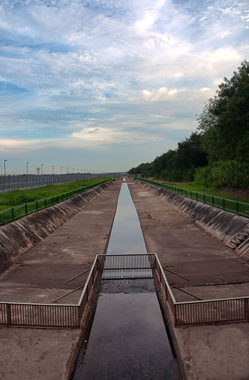 A canal separates the wilderness and Changi Airport's Runway Beauty In Nature Boardwalk Envision The Future Cloudy Day Diminishing Perspective Empty Grass Growth Idyllic Landscape Long Nature No People Outdoors Plant Scenics Sky The Way Forward Tranquil Scene Tranquility Tree Vanishing Point Walkway