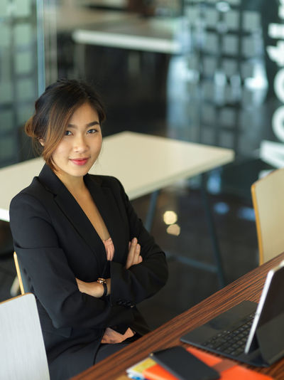Portrait of smiling young businesswoman sitting in office