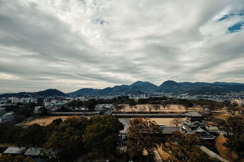 Kumamoto castle with cityscape against cloudy sky
