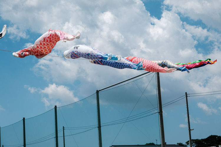 Low angle view of fish flags hanging against sky