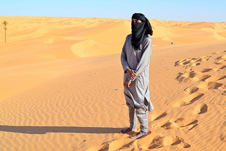 Full length of woman standing on sand dune
