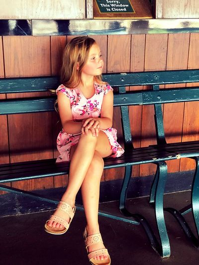 Girl sitting on bench while looking away