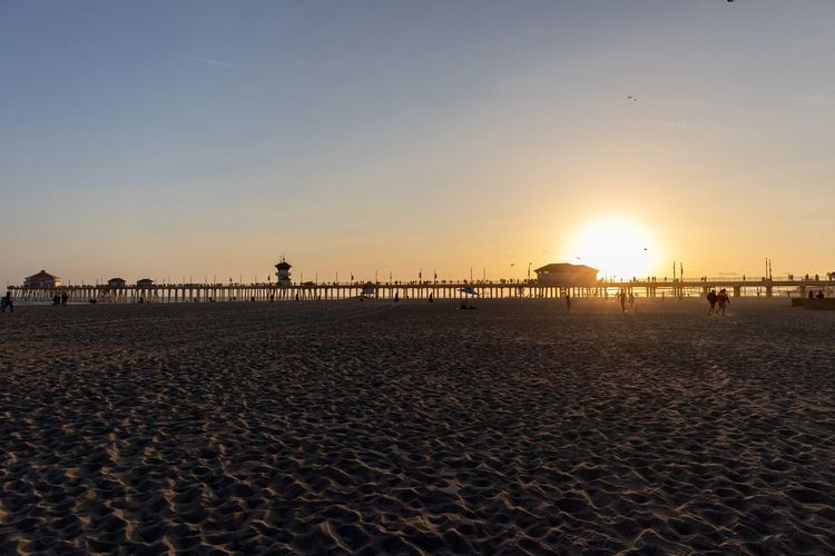 Huntington Beach pier silhouette during sunset Sky Beach Sunset Land Sun Sand Scenics - Nature Beauty In Nature Sea Sunlight Tranquility Water Tranquil Scene Incidental People Nature Orange Color Group Of People Idyllic Non-urban Scene Outdoors Huntington Beach Orange County