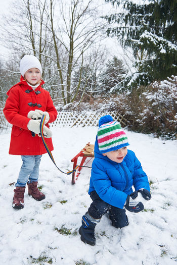Siblings playing with snow on field during winter