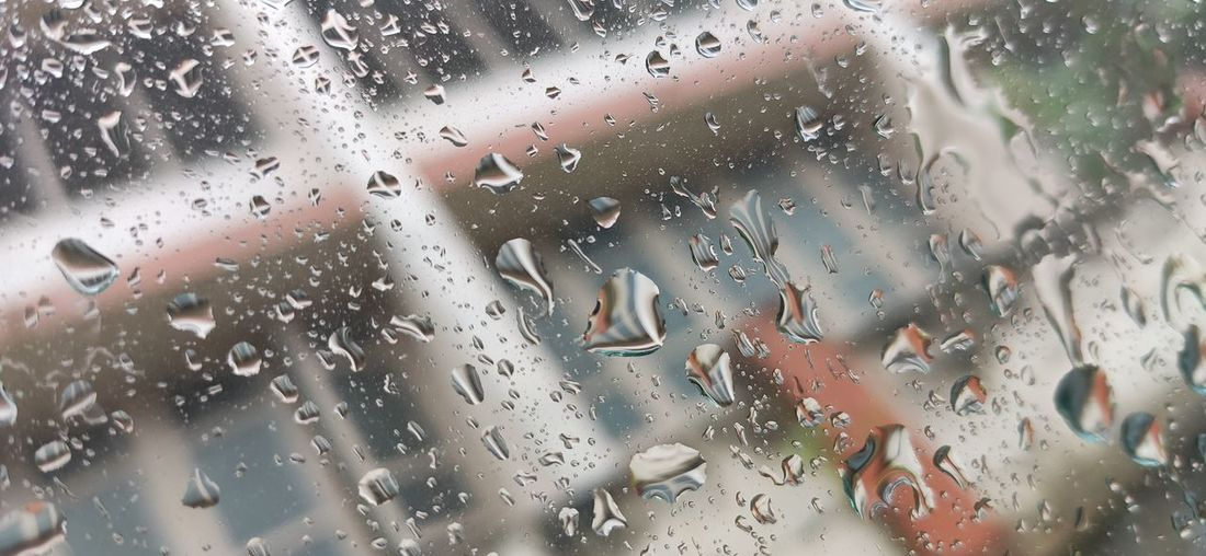 Full frame shot of wet glass window during rainy season