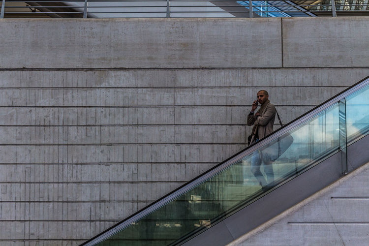 Businessman standing on escalator against wall