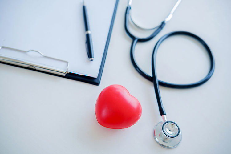 Directly above shot of heart shape and stethoscope with clipboard on gray background