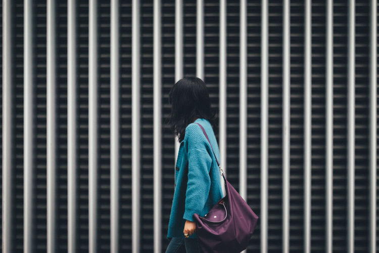 Woman walking against building