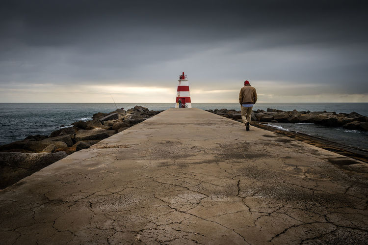 Man walking out to a lighthouse Beauty In Nature Calm Cloud Cloud - Sky Day Horizon Over Water Idyllic Lighthouse Man Walking From Behind Nature Outdoors Remote Scenics Sea Shore Sky The Way Forward Tranquil Scene Tranquility Water