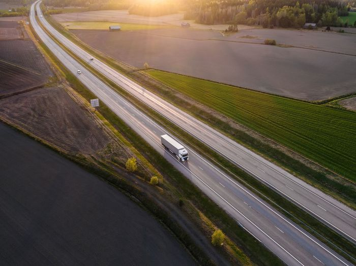 High angle view of truck on street amidst agricultural field during sunset