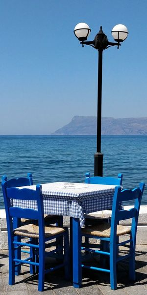 Empty chairs and table by sea against clear blue sky