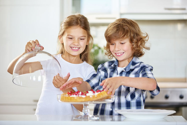 Siblings Making Cake In Kitchen At Home