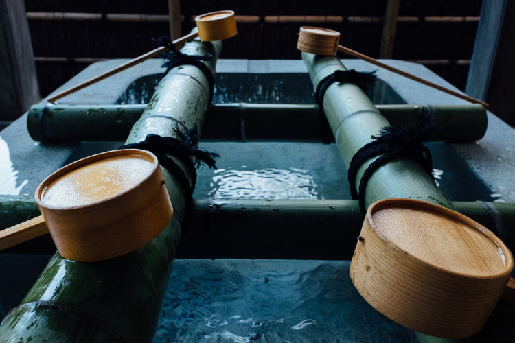 Close-up of wooden ladles at trough