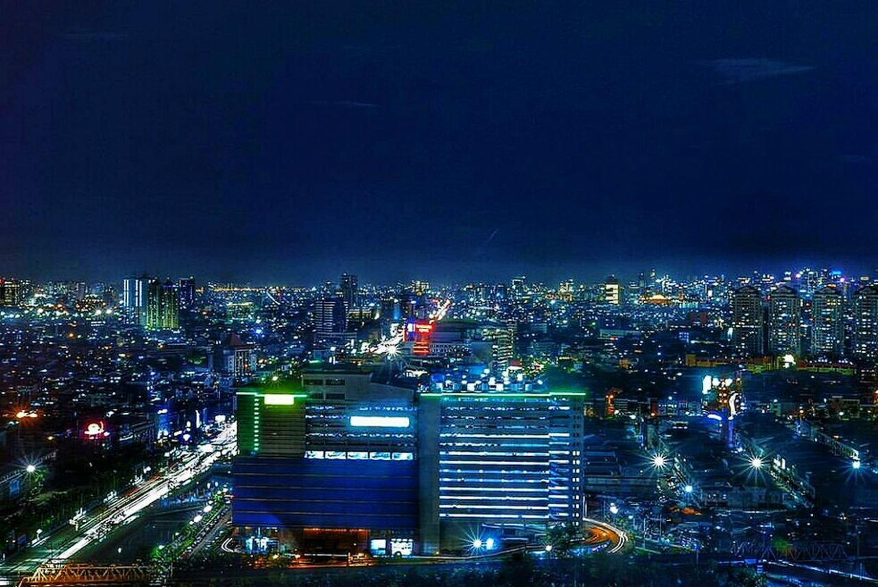 night, illuminated, cityscape, city, high angle view, architecture, skyscraper, aerial view, city life, urban skyline, building exterior, no people, built structure, travel destinations, modern, outdoors, sky, neon