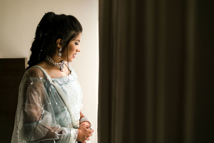 Side view of a young woman looking through window