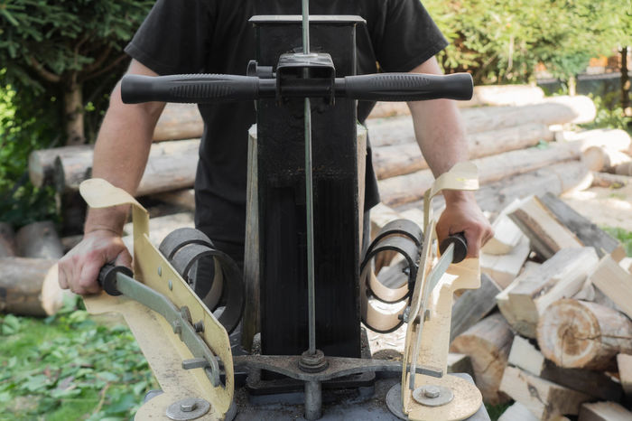 Firewood split with wooden splitter Wood Wood Splitting Body Part Cutter Day Human Hand Low Section Men Nature Outdoors People Real People Sharp Sitting Transportation Wheelchair