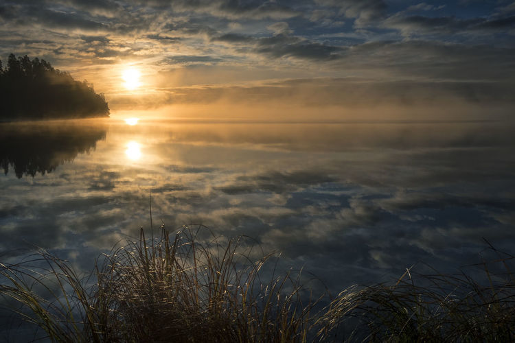 Scenic landscape with beautiful sunrise in the lake. Beauty In Nature Cloud - Sky Clouds And Sky Dramatic Sky Dusk Fog Foggy Hay Horizon Over Water Landscape Mist Misty Morning Nature No People Outdoors Reflection Scenics Sea Sun Sunlight Sunrise Sunset Water