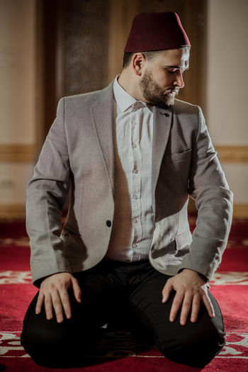 Young man praying while sitting at mosque