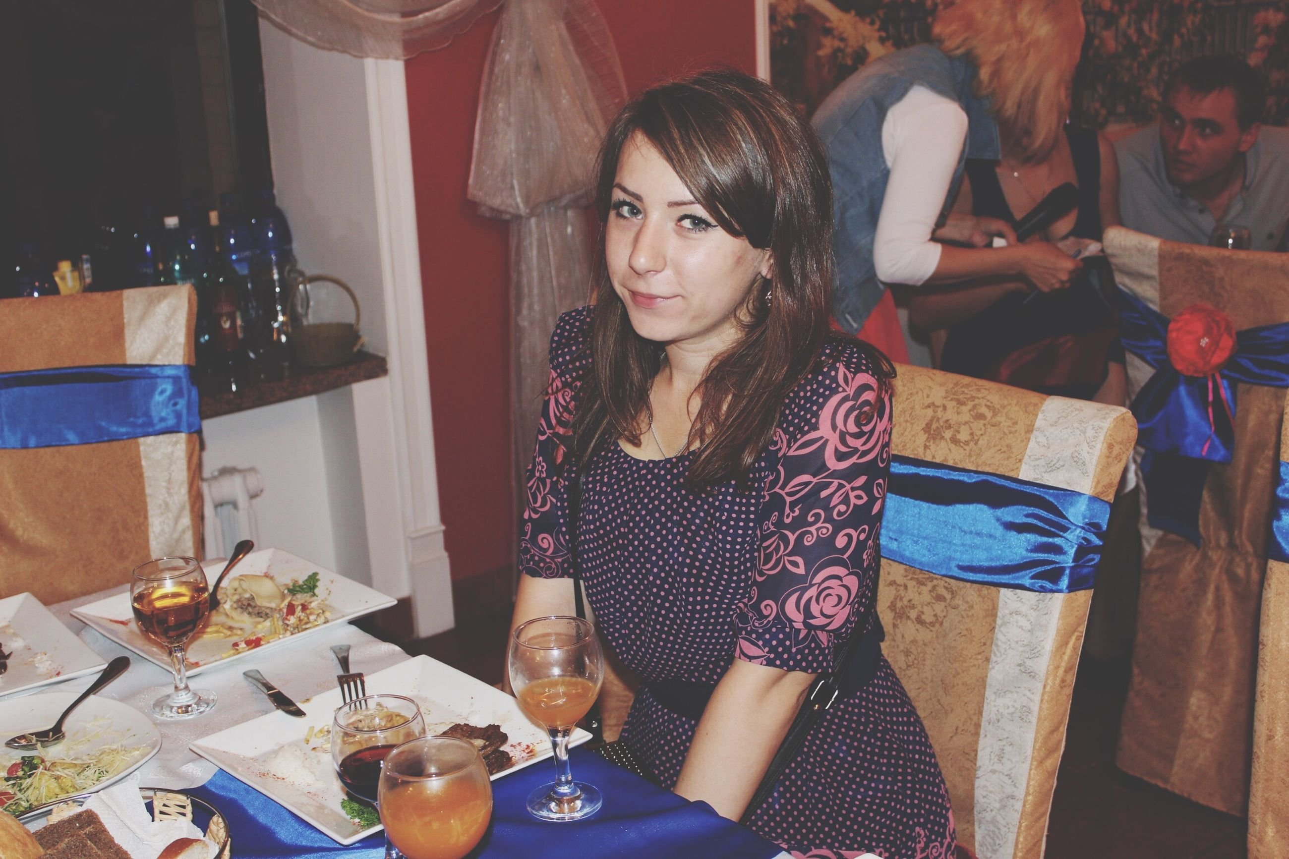 indoors, food and drink, lifestyles, casual clothing, table, young adult, leisure activity, person, front view, holding, portrait, drink, young women, looking at camera, food, restaurant, waist up, sitting